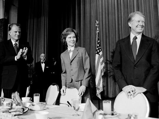 The Rev. Billy Graham, left, applauds President Jimmy