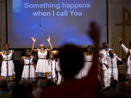 """Grace Wanyana (center), 19, of Uganda, with the Imani Milele Choir, leads a worship song May 7, 2017, at Christ by the Sea United Methodist Church in Vero Beach. The choir is part of Imani Milele Children, a Christian organization whose stated mission is to """"rescue, educate, develop and improve lives of Uganda's orphaned and most vulnerable children."""""""