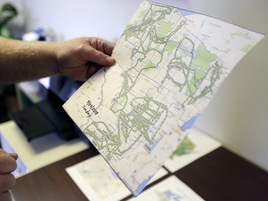 Mike Callahan, a pilot with the state Department of Natural Resources, holds a map that shows flight paths taken by pilots across the state on a single day.