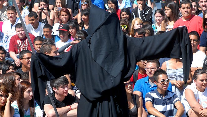 The grim reaper looms over the crowd of Las Cruces High School students who were watching the scene of a mock crash involving their peers in 2012. A similar event will take place Thursday at Mayfield.