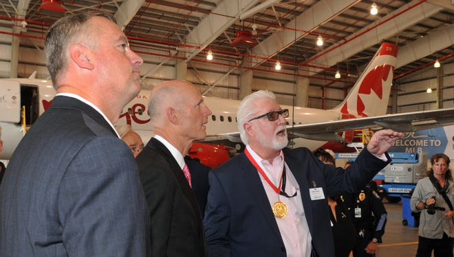 Greg Donovan, executive director of Orlando Melbourne International Airport, Florida Governor Rick Scott , and Gary Girard, president of AeroMod International at a press conference held inside their hangar at Orlando Melbourne International Airport. AeroMod has announced 150 new jobs and there current facility, and an expansion that will hopefully add an additional 10 jobs later.