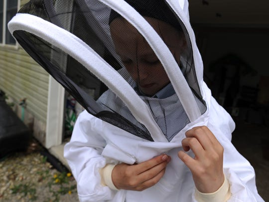 Madison Johnson puts her her beekeeper's jacket and veil Wednesday at her home near Thornville.