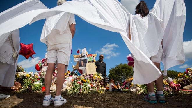 """Courtney Mark, 56, pays his respects at the memorials set up outside Marjory Stoneman Douglas High School during back to school orientation day in Parkland on Sunday, Feb. 25, 2018. """"It's too close to home not to come,"""" Mark said. """"These could have been our kids."""""""