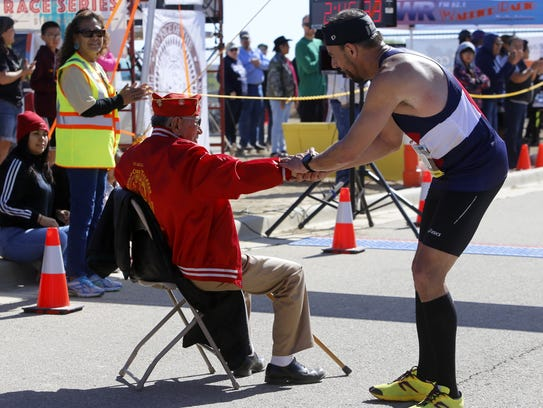 Runner Troy Eid shakes hands with Navajo code talker John Kinsel Sr. Saturday after crossing the finish line.