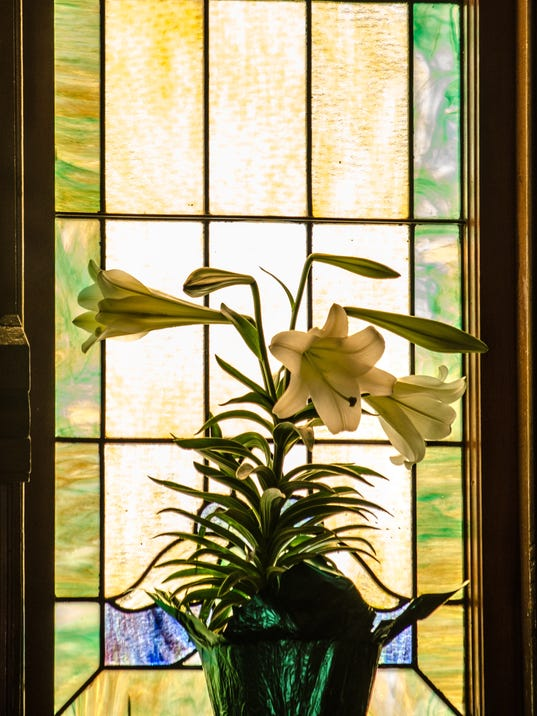 Easter lillies against a stained glass window