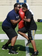 Coach Alonzo Jackson, Jr. does drills with camper Terreyon