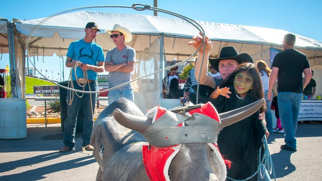 Itzel Velasco-Torres, 4, dressed up for Halloween, ropes a practice steer with the help of New Mexico State rodeo team member Josh Davison on Saturday during the third Ag Day Street Fair on the NMSU campus.