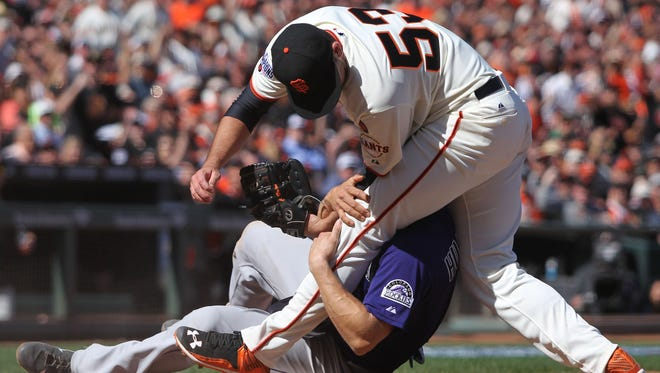 Giants starting pitcher Chris Heston gets tangled up with Rockies catcher Nick Hundley, who scored the game's second run.