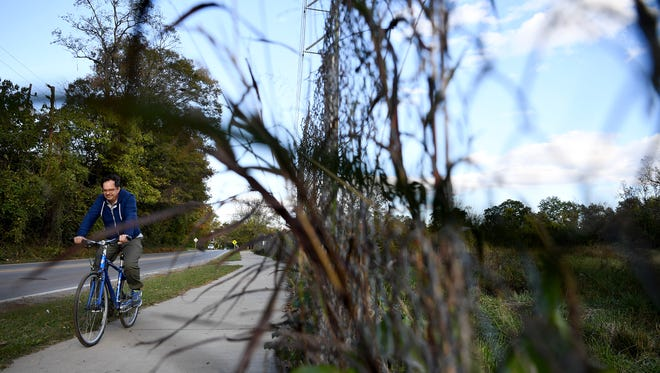 In this file photo from October 2017, a man rides a bicycle on the sidewalk next to Amboy Road along the French Broad River Greenway next to the fence surrounding the Karen Cragnolin River Park.