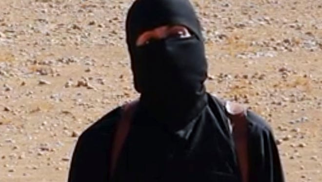 """FILE - This undated image shows a frame from a video released Friday, Oct. 3, 2014, by Islamic State militants that purports to show the militant who beheaded of taxi driver Alan Henning . A British-accented militant who has appeared in beheading videos released by the Islamic State group in Syria over the past few months bears """"striking similarities"""" to a man who grew up in London, a Muslim lobbying group said Thursday Feb. 26, 2015. Mohammed Emwazi has been identified by news organizations as the masked militant more commonly known as """"Jihadi John."""""""