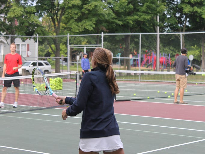 Partners from Dealer.com and Patagonia work with members of the King Street Center's tennis program Wednesday morning.