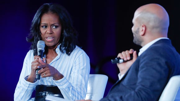 Former first lady Michelle Obama talks with Sam Kass,
