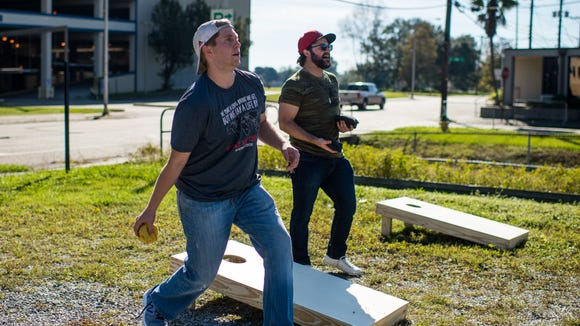 Kyle Patton and Ross Fontenot throw beanbags while playing cornhole at Olympic Grove in Lafayette. The Grove brings yard games to E's Kitchen this weekend.