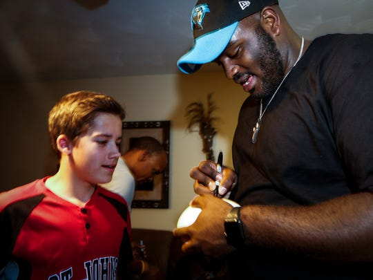 Former Western Michigan University football standout, Okemos native Taylor Moton autographs a football for Murray Palmatier, 12, of St. Johns Friday evening, April 28, 2017, at the NFL draft watch party at Moton's parents' home.  Moton was the final pick in the second round of the 2017 NFL draft and will play for the Carolina Panthers.