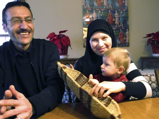 Syrian refugee Ahmed Khatib, left, sits with his wife