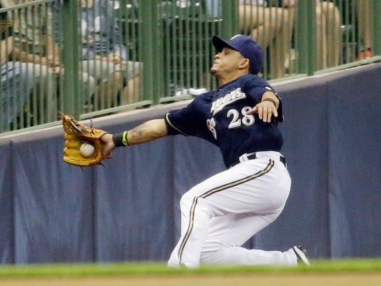 Milwaukee Brewers right fielder Gerardo Parra makes a falling catch on a ball hit by San Francisco Giants' Brandon Crawford during the eighth inning of a baseball game Tuesday, Aug. 5, 2014, in Milwaukee. (AP Photo/Morry Gash)