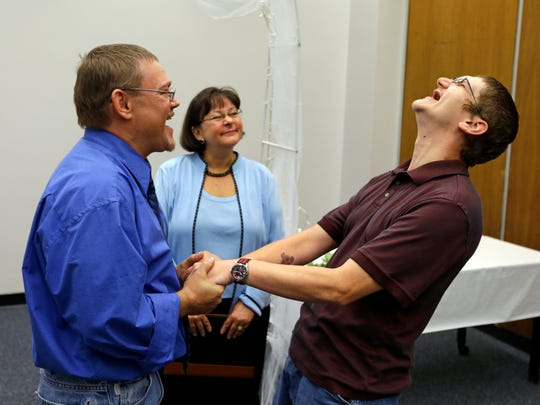 Adam Shoffner, right, shouts his joy after he married Daniel Tolliver, left, as Marion County Clerk Beth White looks on as same sex couple continued to be married for the second day in Indianapolis, Thursday, June 26, 2014. A federal judge struck down Indiana's ban on same-sex marriage Wednesday in a ruling that immediately allowed gay couples to wed. (AP Photo/Michael Conroy)