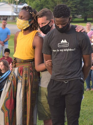 Ashadee Miller (left), her husband Morgan and their adopted son Isaac Slabaugh pray during a vigil last week in Berlin, hosted by The Neighborhood, a group that aims to draw attention to social injustice and racial disparities.