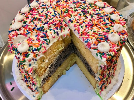 The signature cake at Sugar Hi in Armonk is yellow cake with oreo cream filling, seen here with a decorative rainbow-sprinkle topping.