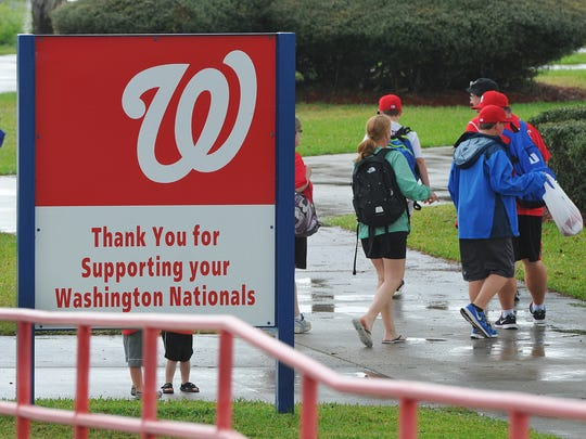 Disappointed Washington Nationals fans walk to their cars after Monday's spring training game against the Florida Marlins was rained out.