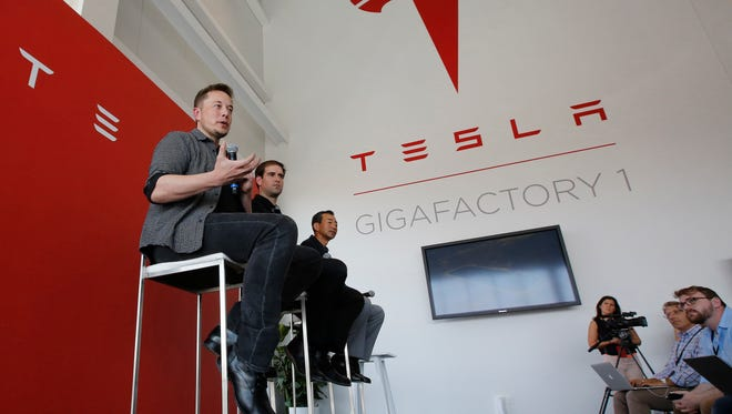 FILE - In this Tuesday, July 26, 2016, file photo, Elon Musk, CEO of Tesla Motors Inc., left, discusses the company's new Gigafactory in Sparks, Nev. On Wednesday, Aug. 3, 2016, Tesla reports financial results. (AP Photo/Rich Pedroncelli, File) ORG XMIT: NYBZ301