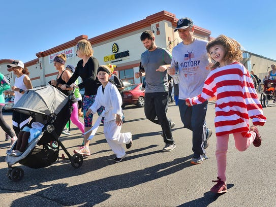 Runners, some dressed in costume, start on a 5K fun