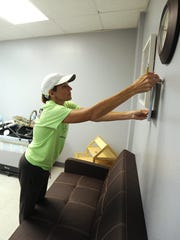 Volunteer Rhea Rodriguez hangs artwork in one of the remodeled visitation rooms at the CPS building on Sept. 10.