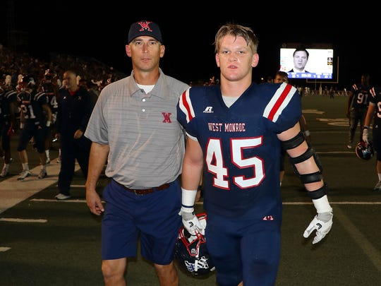 West Monroe assistant coach Joey Adams (left) and senior linebacker Jacob Adams (right) walk on the field for the final Thanksgiving as coach and player.