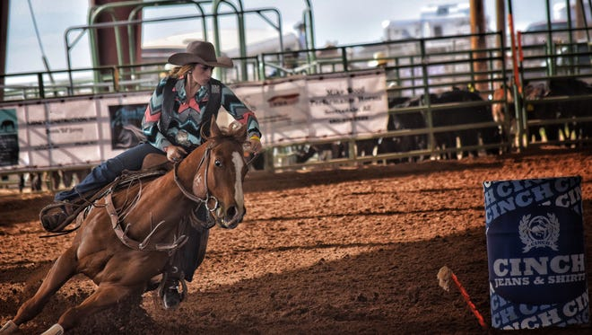 New Mexico State University rodeo athlete Anna Barker competes in the barrel racing event during the Las Cruces Rodeo.