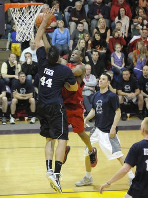 Jamie Feick (Lexington) challenges a shot by Terrence Davison (Mansfield Senior) in the 35th News Journal All-Star Basketball Classic alumni game. Looking on is Nate Reinking (Galion), now the head coach of the Canton Charge, the Cleveland Cavaliers' G League team.