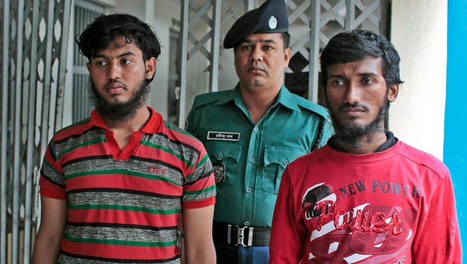 A Bangladeshi policeman escorts Jikrullah, left, and Ariful Islam, two suspects in the meat-cleaver death of a blogger in Dhaka, Bangladesh, on Monday, March 30, 2015.