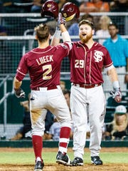 Florida State sophomore Jackson Lueck (2) in congratulated by teammate Quincy Nieporte after hitting a solo shot in the eighth inning.