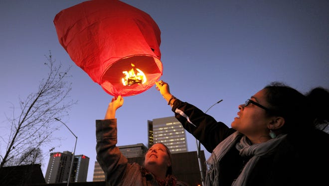 "Melissa Emmal and Soma Kliemann release a sky lantern in Anchorage to spread awareness about violence against women.  Emmal said the lanterns were released ""to honor those we have lost, and offer a glimmer of hope to those who are still suffering."""