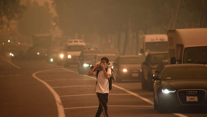 A man leaving Santiago Canyon College in Orange, Calif., looks back as strong Santa Ana winds blow fire and smoke toward the college on Oct. 9, 2017. Another Santa Ana wind event is forecast for Monday and Tuesday.