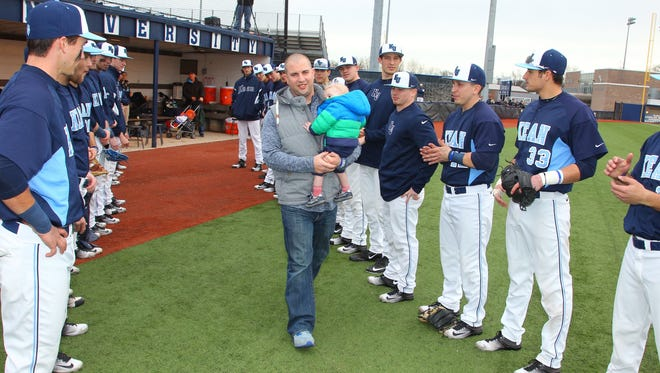 Mike O'Donnell carries 13-month old son Shane onto Kean University baseball field during Sunday's pre-game ceremony