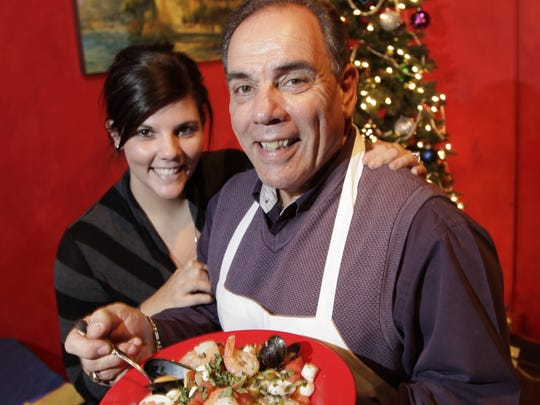 Harry Stephens with, flanked by daughter Allison Allender, with a seafood stew prepared for Bella Luna's Feast of Seven Fishes, an Italian Christmas tradition.