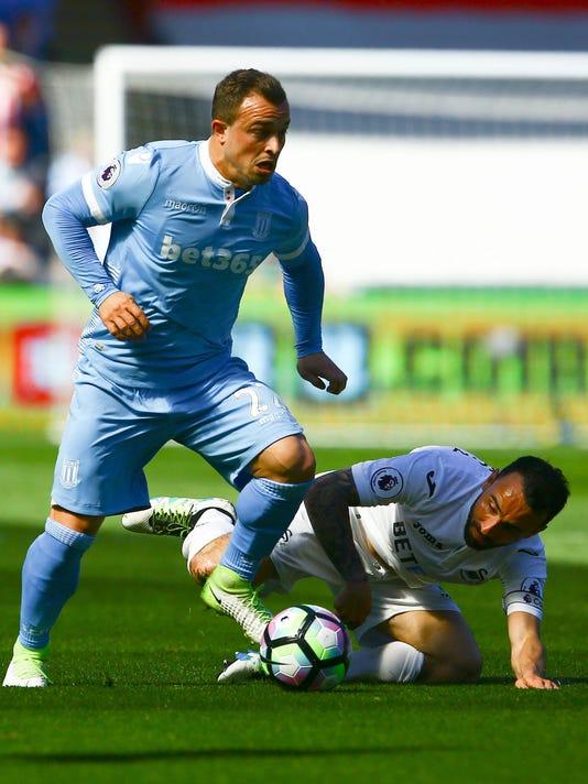 Stoke City's Xherdan Shaqiri, left, and Swansea City's Leon Britton battle for the ball during their English Premier League soccer match at the Liberty Stadium, Swansea, England, Saturday, April 22, 2017. (Geoff Caddick/PA via AP)
