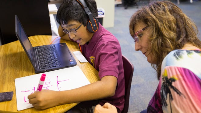 Aasim Raheem gets assistance from instruction coach Kym Tolway during math class at Arizona Autism Charter School in Phoenix on Sept. 22, 2017. The school serves about 180 students in grades K-8, and all of them have special needs.