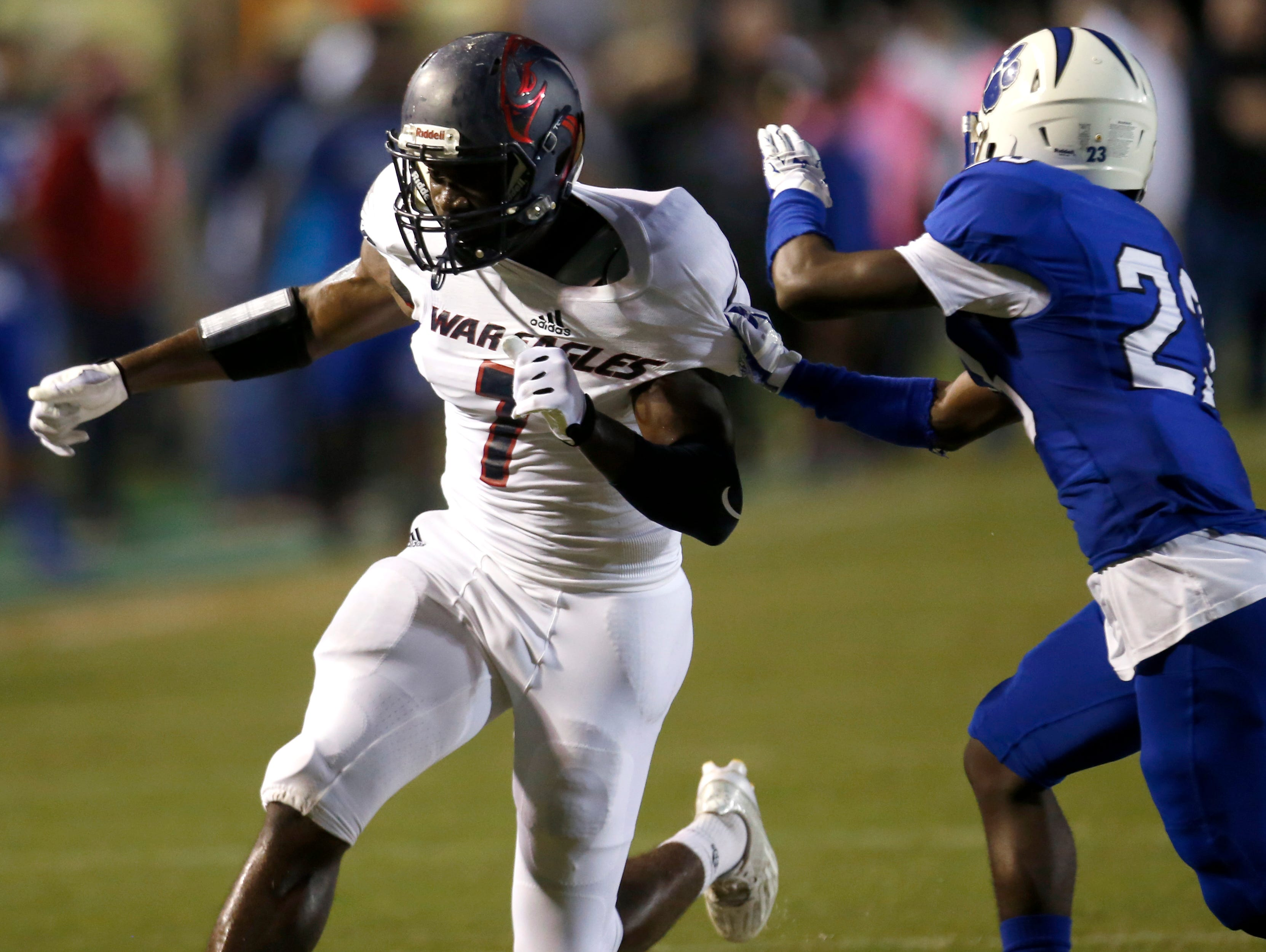 Wakulla's Keith Gavin is held by a Godby defender during their game at Cox Stadium on Thursday.