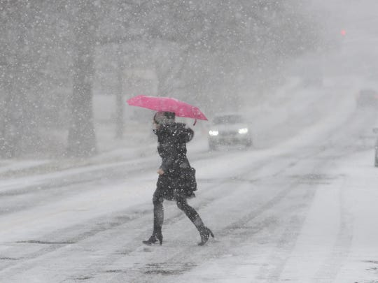 A woman runs in the snow across Morlot Ave to catch a New York City bound bus Tuesday morning, January 31, 2017.  Tariq Zehawi/NorthJersey.com