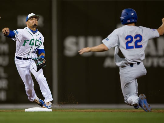 FGCU shortstop Julio Gonzalez turns the double play as Florida's JJ Schwarz slides into second at JetBlue Park Tuesday, March 7, 2017 in Fort Myers, Fla. FGCU would go on to win 7-3.
