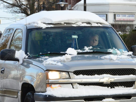 A woman drives her pick up truck along Paterson Ave