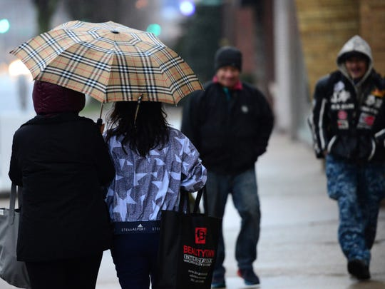 Two women share an umbrella to shield themselves from