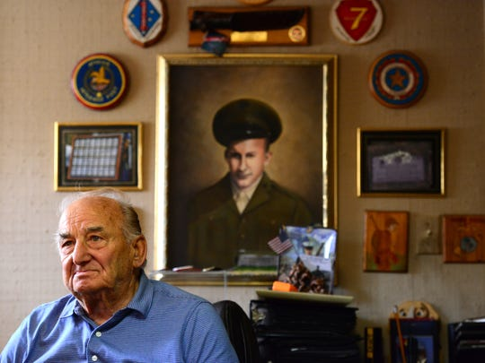 Frank Naider, of Wayne, sits in front of a portrait of his brother William Naider who was killed in action in Okinawa while serving in the Marines during World War II. Naider wanted to find out more about his brother's death and ended up creating a network of WWII era servicemen.