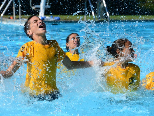 Students do jumping jacks in the pool as they attend