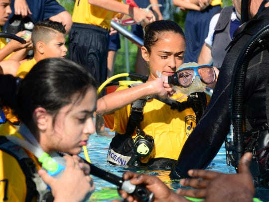 Students get equipped in SCUBA gear at the Bogota Swim