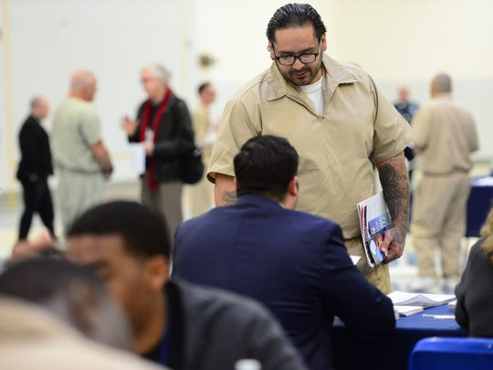 Jose Guzman, of Newark, talks at a table about getting