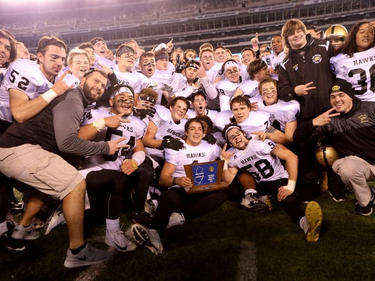 Dave Estevez holds the North 1 Group 3 NJSIAA Football Championship trophy as he is surrounded by his team, Sunday, December 2, 2017,