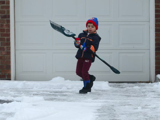 Luca Villani, 4, of Fair Lawn, helps his father clear