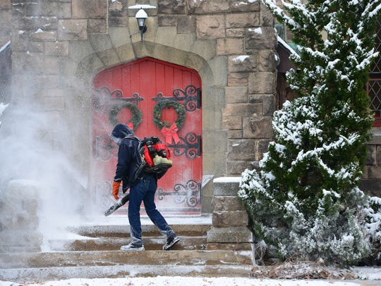 Joshua Tudor uses a leaf blower to clear the snow from